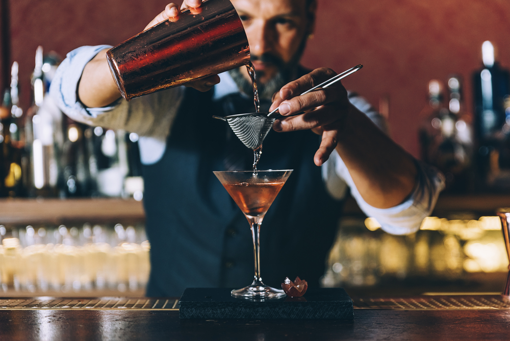bartender pouring alcohol into martini glass