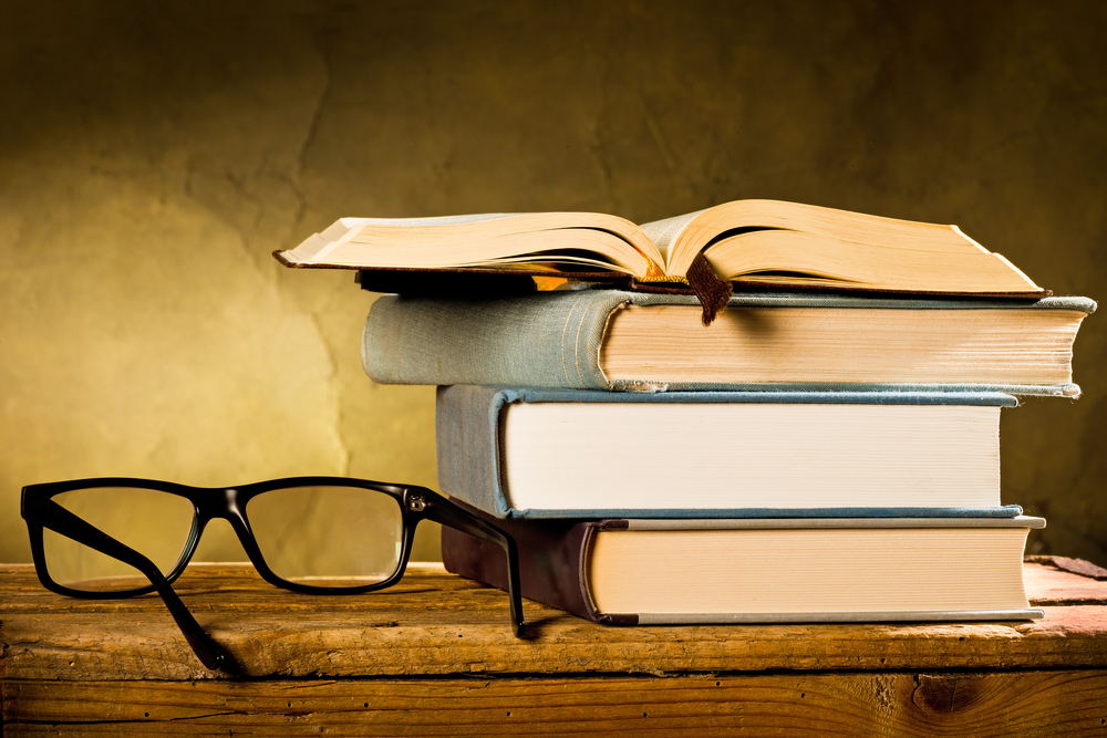 a pile of books next to reading glasses on wooden desk