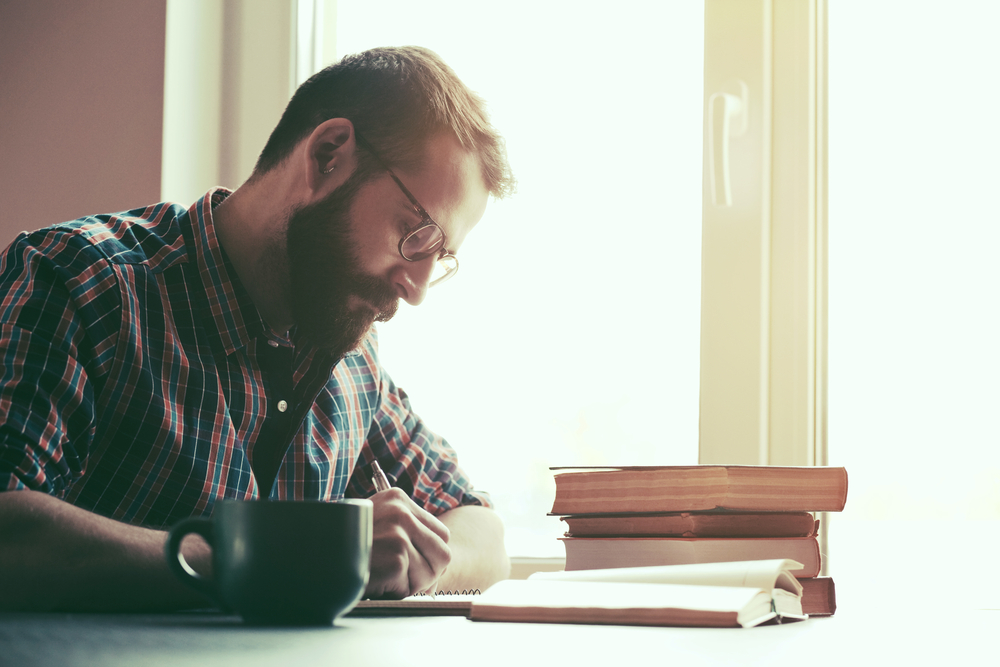 bearded man writing at table