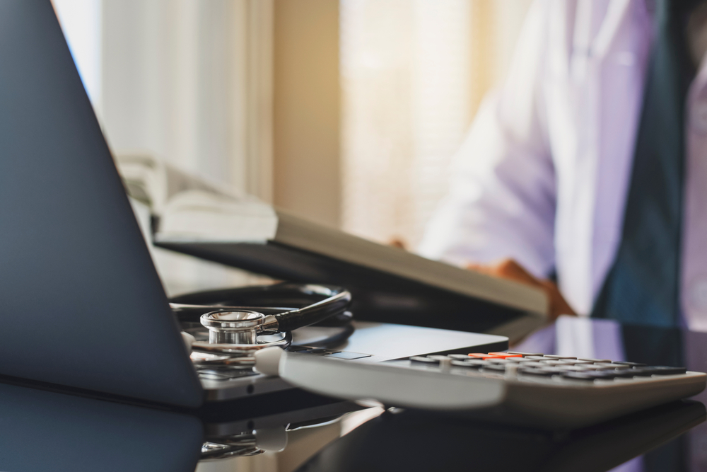 open laptop and calculator in front of doctor reading book